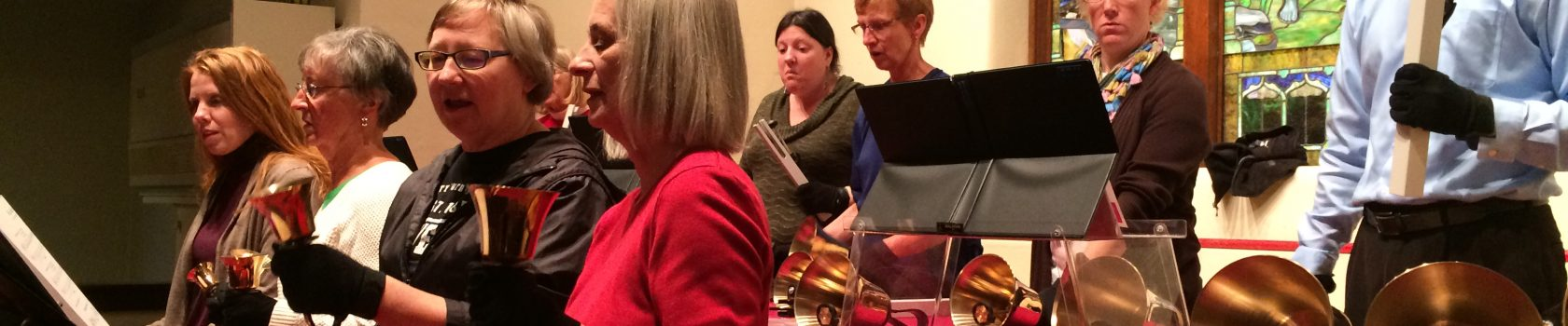 A handbell choir stands playing their bells.